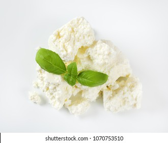 pile of crumbly white cheese on white background