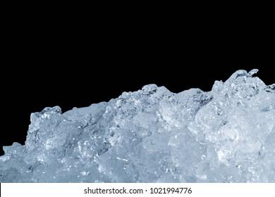 Pile of crushed ice cubes on dark background with copy space. Crushed ice cubes foreground for beverages, beer, whisky, fruit juice, milk, fresh food or fresh vegetables.