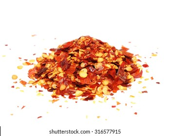 pile crushed red pepper, dried chili flakes and seeds isolated on white background
