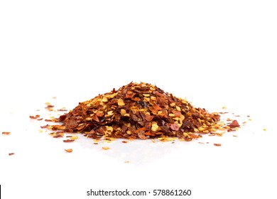 The pile of a crushed red pepper, dried chili flakes and seeds isolated on white background