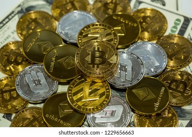 Pile of crypto currency on top of dollar bills, Bitcoin, BTC, dash, ethereum and lite cions, close up isolated.