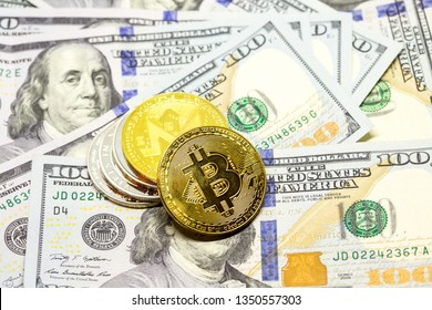 Pile of cryptocurrency coins with bitcoin as first coin displayed on a heap of one hundred dollar bills.