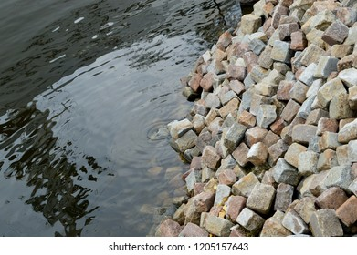 A pile of cubic stones falls into cold, calm water