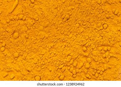 Pile of curcuma powder background texture