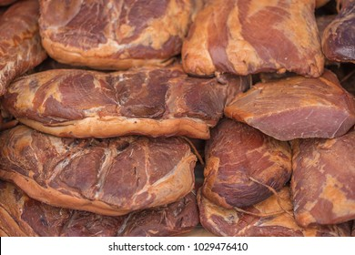 pile of cured ham on market display, shallow focus