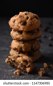 Pile of Delicious Chocolate Chip Cookies with Crumbs on a Dark Background