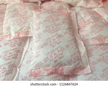"""Pile of Desiccant silica gel, used for moisture protection in the food industry, on packaging has the label clearly labeled """"Desiccant, Silica gel, Throw Away, Do not eat""""."""