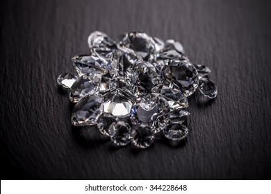 Pile of diamonds on dark metal surface
