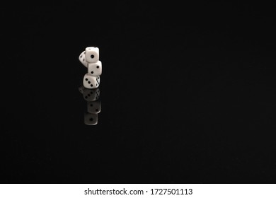 Pile of dices just about to fall on a black table