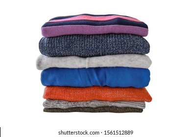 Pile of different colour sweaters on white background. Autumn-winter concept.