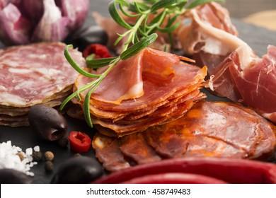 a pile of different spanish embutido, jamon, chorizo and lomo embuchado