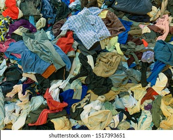pile of different used clothes on sale in a flea market