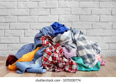 Pile of dirty clothes on floor near brick wall