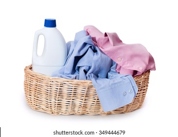 Pile of dirty laundry in a washing baskets in wicker basket with detergents isolated on white background