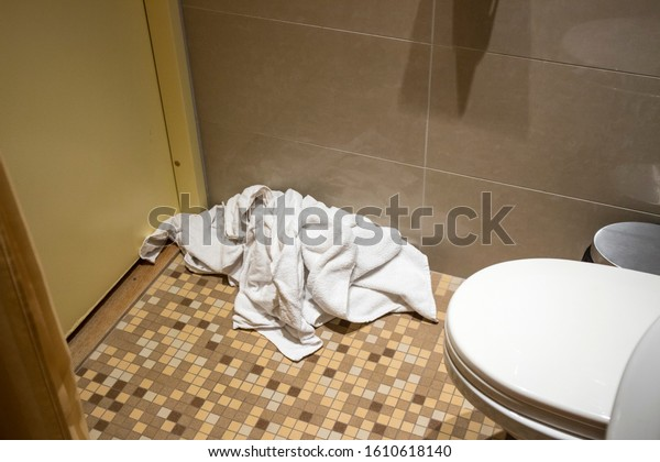 Pile of dirty used towels on the hotel bathroom floor. Housekeeping replace only the used towels on floor with clean ones. Saving water, soap, energy as a green policy.