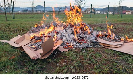 Pile of dismantled cardboard boxes burning in the backyard.