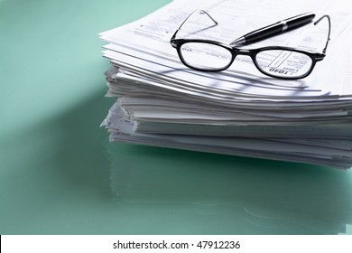 Pile of document with tax form on top, visible though glasses. Focus mainly on 1040.