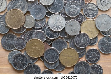A pile of dollar canadian coins on a wood background