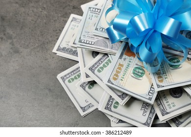 Pile of dollars with bow as gift on grey textured background