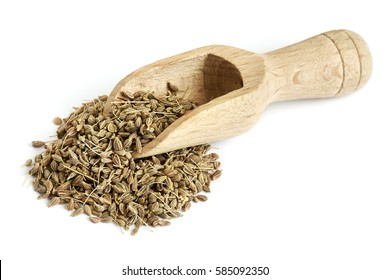 Pile of of dried anise seed (aniseed) with wooden scoop isolated on white background