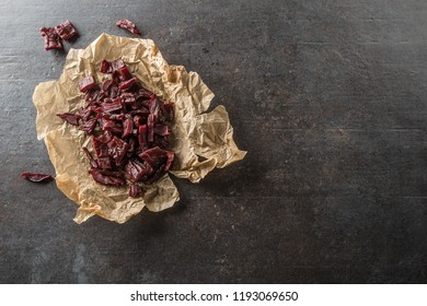 A pile of dried beef jerky pieces on paper and cutting board.