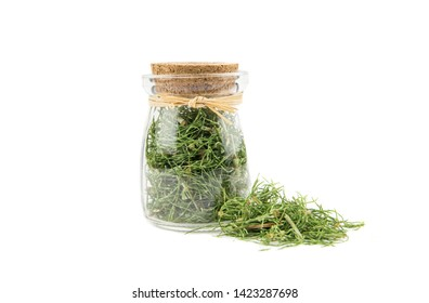 Pile of dried natural herbal medicine called Equisetum arvense the field horsetail or common horsetail isolated on white next to filled glass jar.