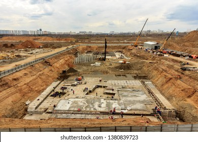 Pile driving in foundation pit for construction of apartment building. Piling driven into ground. Deep foundation installation. Reinforce prestressed concrete piles for factory foundation construction