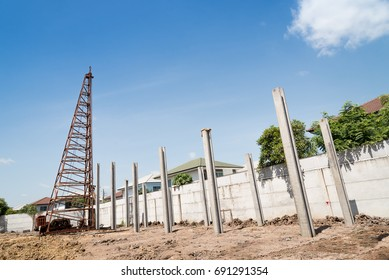 Pile driving machine with reinforced concrete piles on construction site.