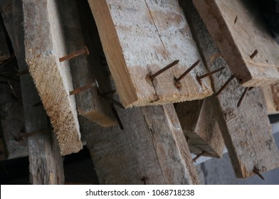 Pile of dusty rustic wooden boards with rusted nails sticking through them stacked haphazardly.