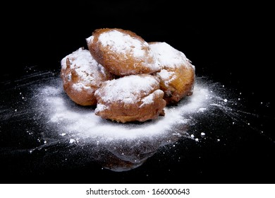 Pile of Dutch donut also known as oliebollen, traditional New Year's eve food isolated over black background