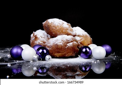 Pile of Dutch donut also known as oliebollen, traditional New Year's eve food isolated over black background and Christmas balls