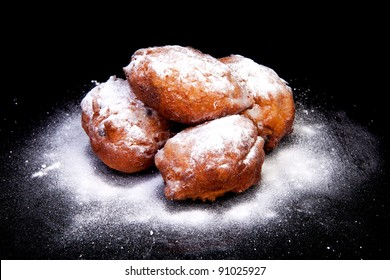 pile of Dutch donut also known as oliebollen with powdered sugar, traditional New Year's eve food isolated on black background