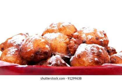 pile of Dutch donut also known as oliebollen with powdered sugar in closeup, traditional New Year's eve food over white background