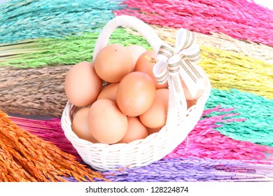 Pile of eggs in basket on Colorful ears of rice