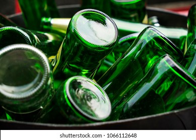 Pile of empty beer, green glass bottles, invert bottom up collected in steel bin for recycle selling. Container industry or waste management concept.