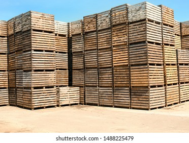 Pile of empty wooden crates outdoors on sunny day