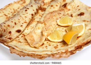 A pile of English-style pancakes (or crepes) on a plate with slices of lemon. The pancakes are served, usually with lemon and sugar, on Shrove Tuesday (Mardi Gras) as well as being year-round treat.