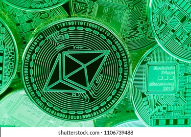 A pile of Ethereum (ETH) physical cryptocurrency coins shot under a green light which gives them a cyberpunk mood