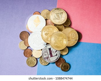 Pile of Euro coins and Crypto currency coins on a colored background, featuring Bitcoin, Ethereum, Iota, Z Cash and Litecoin