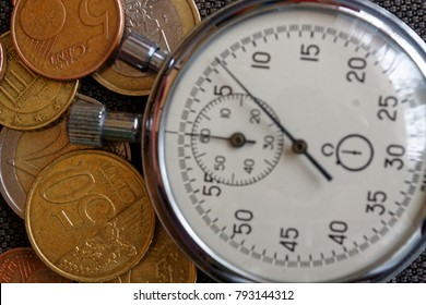 Pile of euro coins with old vintage stopwatch on brown denim background