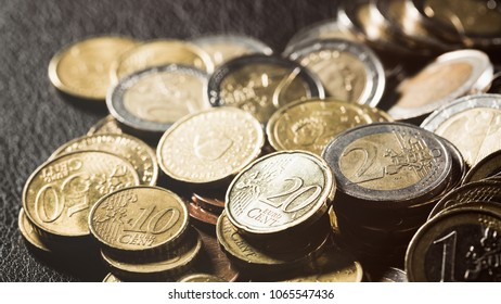 A pile of Euro coins over a black leather surface.