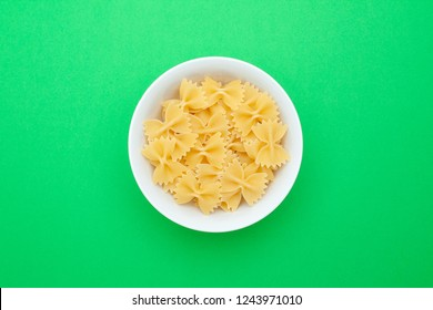 A pile of farfalle pasta in a small white bowl on a green background