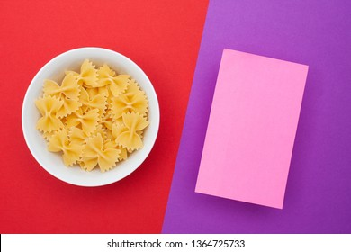 A pile of farfalle pasta in a small white bowl on a red background and purple space with sticker