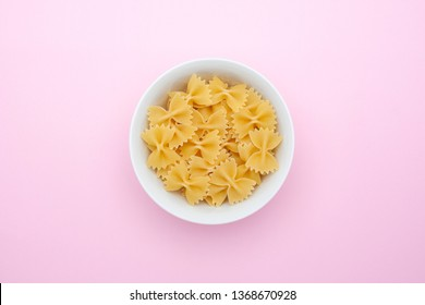 A pile of farfalle pasta in a small white bowl on a pink background