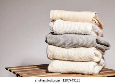Pile of Fashion Warm Sweaters on Wooden Table. Autumn and Winter Wool Clothes. Knitted Sweater or Jacket. Tender Colors. Conditioning and Washing