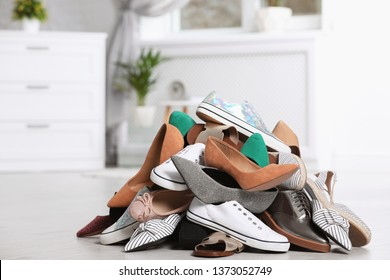 Pile of female shoes on floor indoors