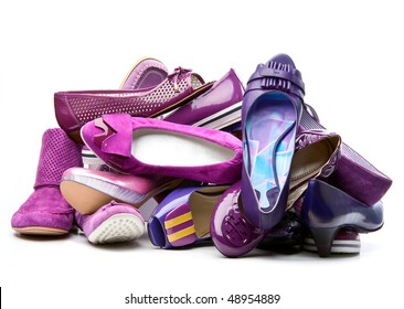 Pile of female violet shoes isolated on white background