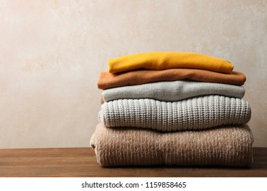 Pile of female warm sweaters on wooden table on neutral background. Concept autumn clothes.