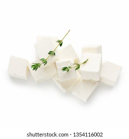 Pile of feta cheese cubes and oregano sprigs on white background
