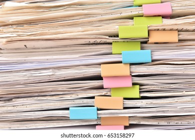 Pile of Financial documents with colorful clips on wood desk stack up,back isolated background
